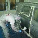 Medewerker 'Van Eeks' bezig met het spuiten van een auto